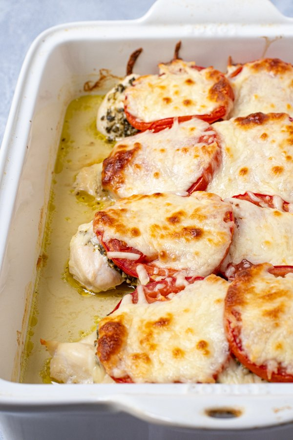 side view of a white baking dish with baked pesto chicken topped with mozzarella cheese.