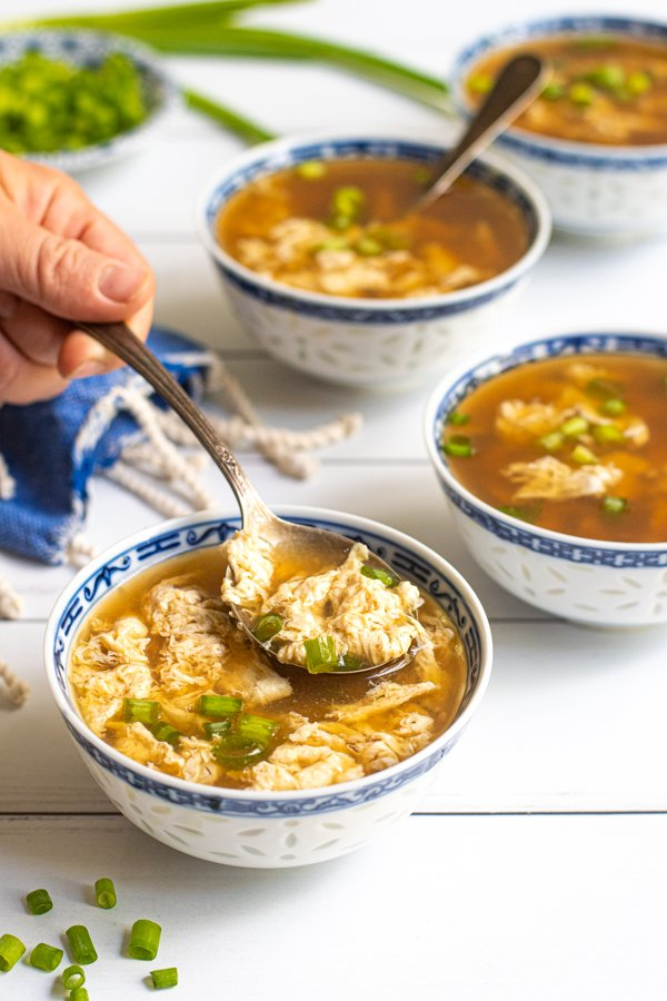 A spoon in a bowl of egg drop soup, garnished with green onions.