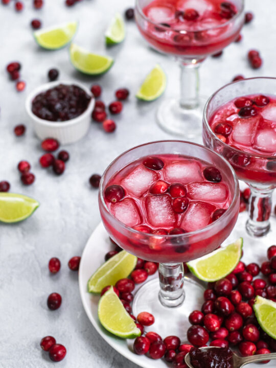 Margarita glasses filled with bright red cranberry sauce margarita and ice, the table that they are on is filled with fresh cranberries and lime slices.
