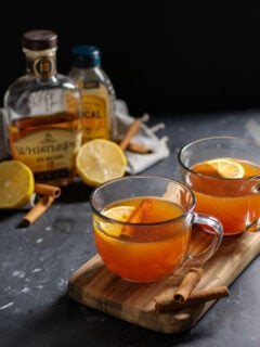 Two clear mugs on a wooden cutting board against a black background filled with hot toddy cocktail and garnished with cinnamon sticks and a lemon wedge.