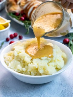 Turkey Gravy From Pan Drippings in a small glass creamer being poured onto a huge bowl of mashed potatoes, the gravy forming a large pool in the center.