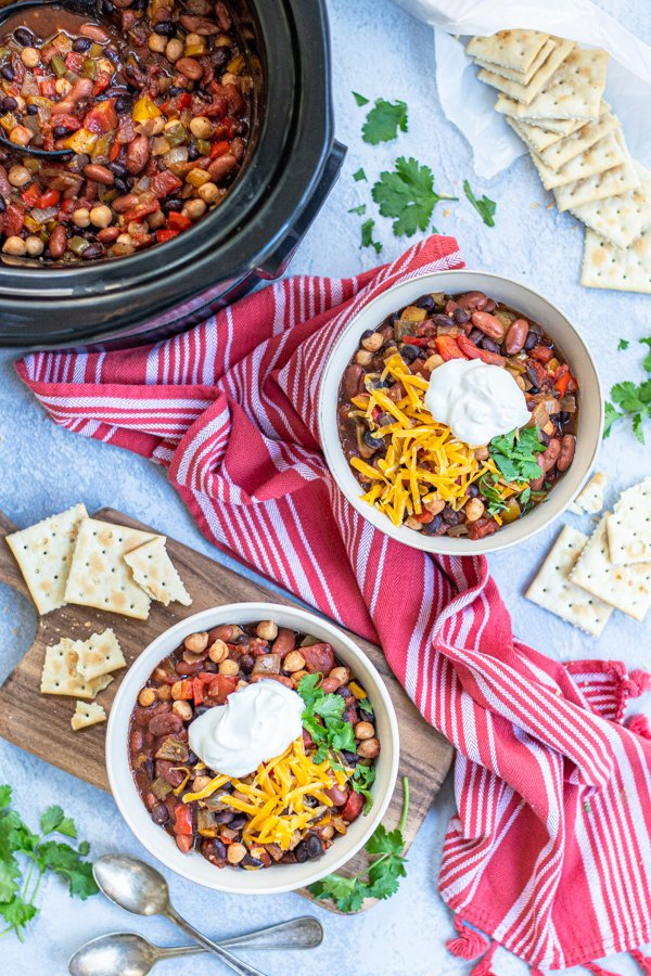 Two bowls and a crockpot full of Three Bean Vegetarian Chili on a table top with garnishes, saltine crackers, a kitchen towels.