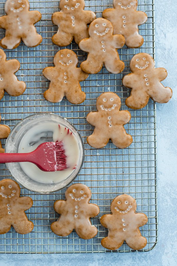 Soft Glazed Gingerbread Cookies arranged out on a wire cooling rack with a bowl and brush full of glaze.