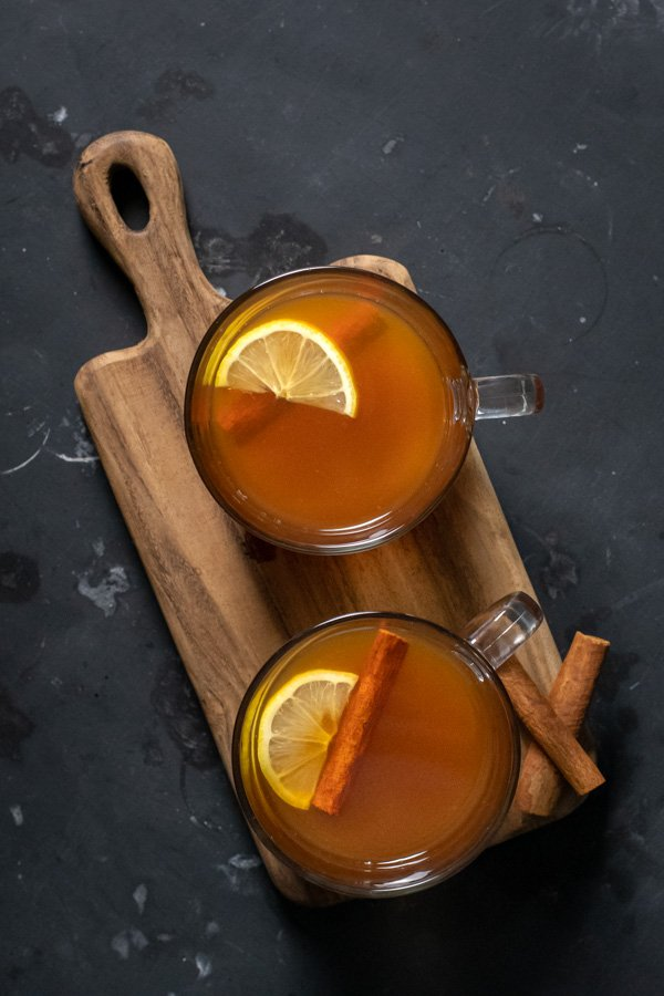 Flatly of a Hot Toddy with Tea Recipe showing two clear mugs filled with a golden liquid and garnished with a cinnamon stick and a lemon slice.