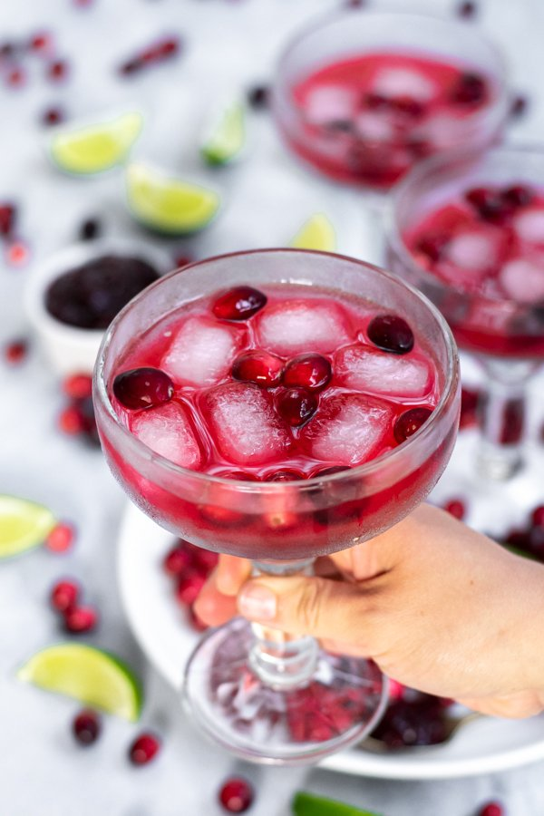 Hand holding a margarita glass filled with a bright red drink and garnished with fresh cranberries.