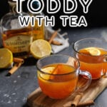 Pinterest Pin with text overlay 'Hot Toddy with Tea'. Image of a clear mug filled with hot toddy and garnished with a cinnamon stick and lemon slice.
