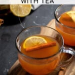 Pinterest Pin with text overlay 'How to make a Hot Toddy with Tea'. Image of a clear mug filled with hot toddy and garnished with a cinnamon stick and lemon slice.