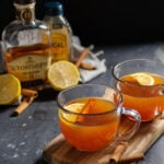 Pinterest Pin with text overlay 'Hot Toddy with Tea, the perfect comforting cocktail'. Image of a clear mug filled with hot toddy and garnished with a cinnamon stick and lemon slice.