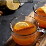 Pinterest Pin with text overlay 'Hot Toddy with Tea, warm & cozy for winter'. Image of a clear mug filled with hot toddy and garnished with a cinnamon stick and lemon slice.