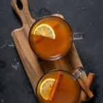 Pinterest Pin with text overlay 'Toddy with Tea, som warm & cozy for winter'. Image of two clear mugs filled with hot toddy and garnished with a cinnamon stick and lemon slice.