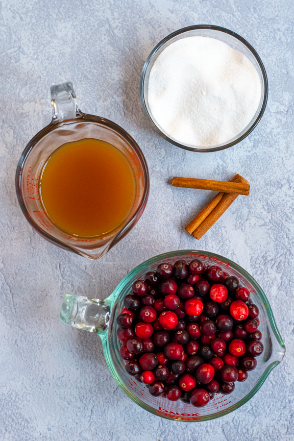 Ingredients needed to make cranberry sauce laid on a table including fresh cranberries, apple cider, sugar, and cinnamon sticks.
