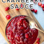 Pinterest Pin with text: Homemade Cranberry Sauce. Image of bowl of cranberry sauce next to loose cranberries.