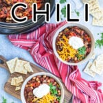 Pinterest Pin with text overlay, Three Bean Crockpot Chili. Image of two bowls and a crockpot of chili on a table with spoons, saltines, and a red kitchen towel.
