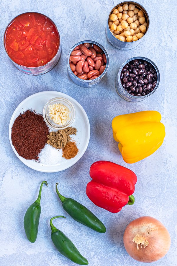 Ingredients needed to make slow cooker vegetarian chili all laid out on a table.