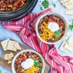 Pinterest Pin with text overlay, The Best Crockpot Vegetarian Chili. Image of two bowls and a crockpot full of chili on a Tavel with spoons, saltine crackers, and a red kitchen towel.