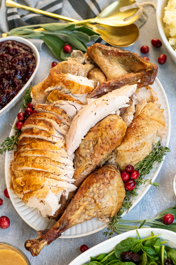 A large white platter with carved dry brined turkey sit-in non a thanksgiving table surrounded by side dishes.