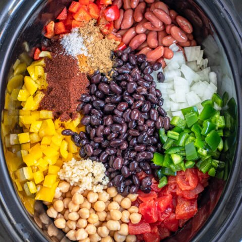 All of the ingredients for easy vegetarian chili laid out nicely in the black crock of a slow cooker.