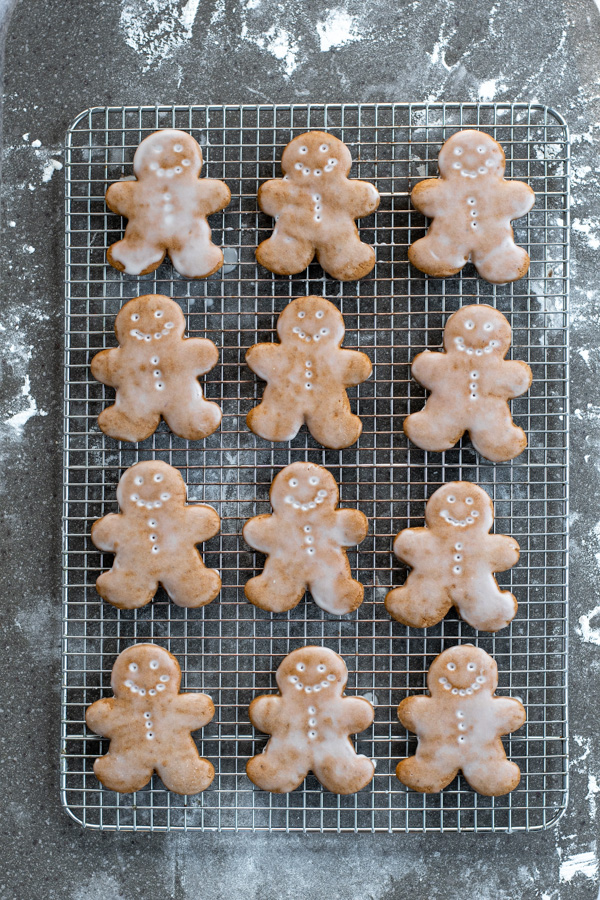 A wire cooling rack full of freshly glazed gingerbread cookies showing off the face and button designs.