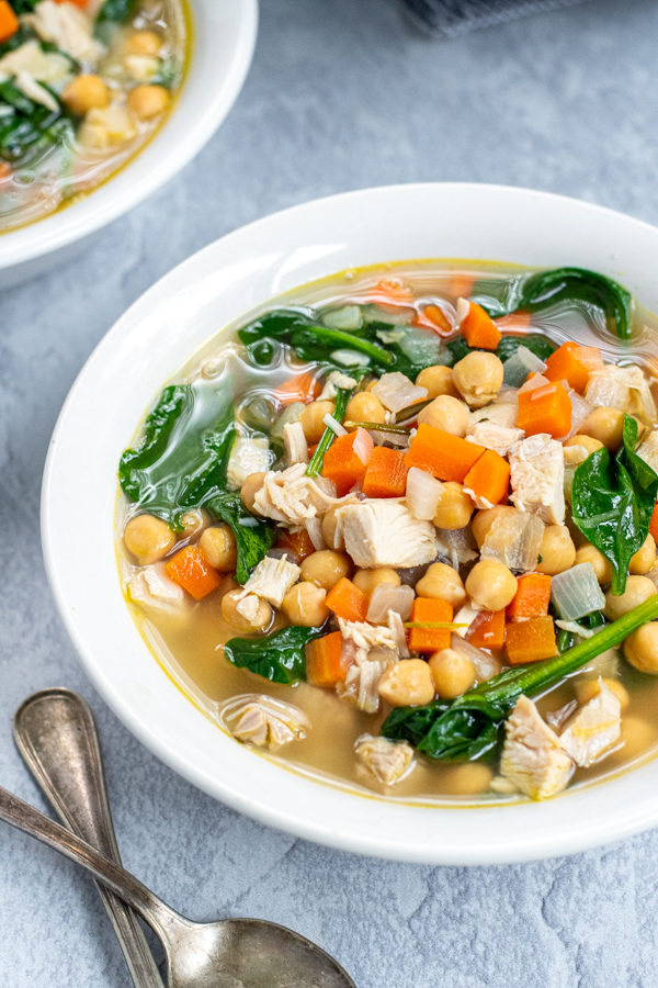 Close up on a white bowl filled with turkey soup with carrots, beans, and healthy spinach.