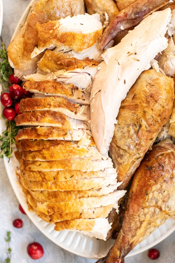 Close up of sliced turkey breast showing golden brown skin and a moist looking piece of turkey tender meat.