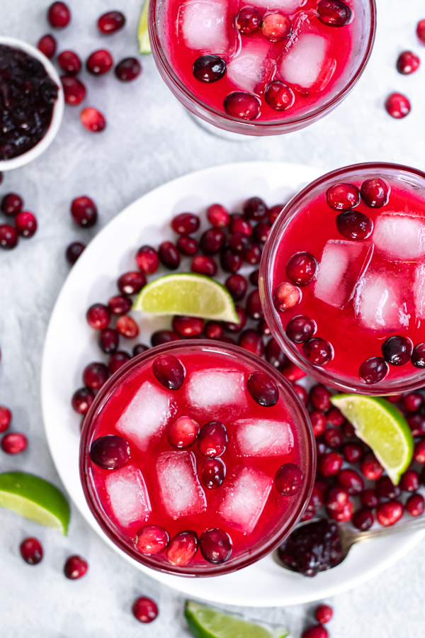 Overhead view of three margarita glasses filled with a bright red drink and ice garnish with fresh cranberries, in addition fresh cranberries are all over the table.