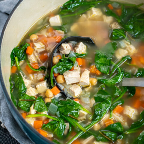 Ladle in a pot of healthy leftover turkey soup filled with chunks of turkey, spinach, chickpeas, and carrots.
