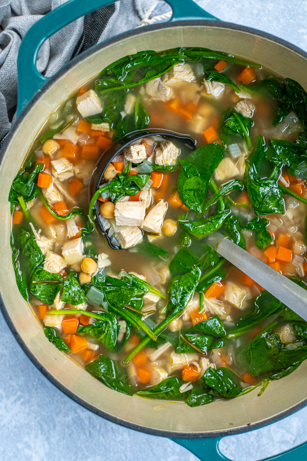 Large dutch oven filled with a colorful turkey soup including turkey chuck, bright spinach, and diced carrots.