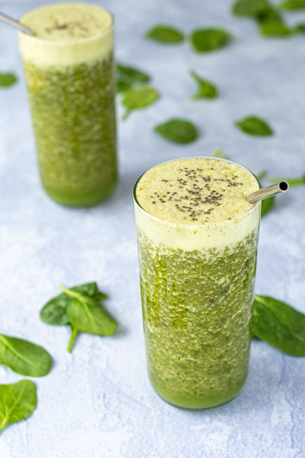 A pair of glasses at an angle filled with green smoothie topped with chia seeds.