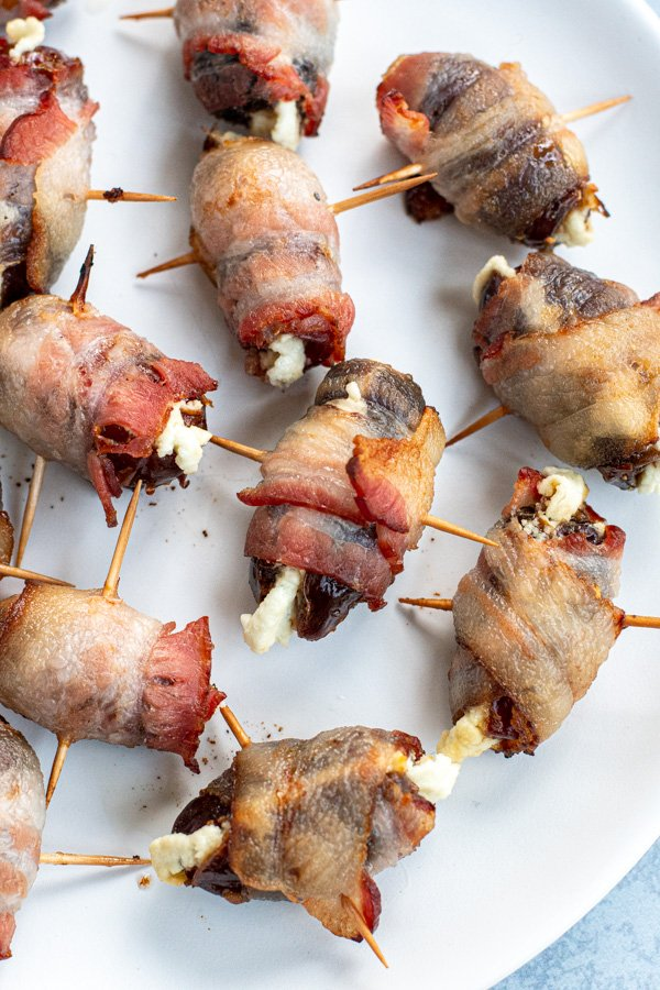 Close up of a goat cheese stuffed bacon wrapped date showing crispy bacon wrapped in place with a toothpick and melty goat cheese coming from the center.