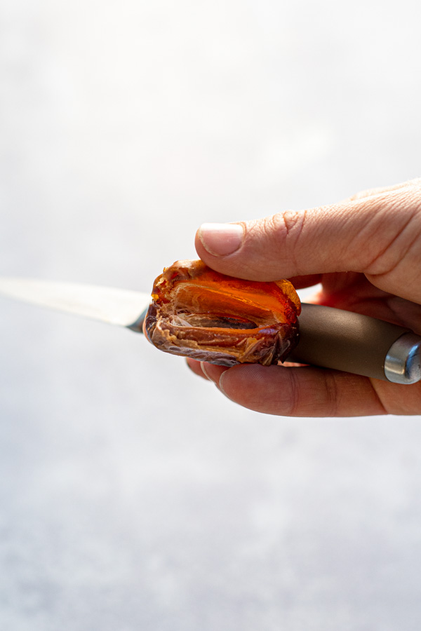 A hand holding a paring knife and a sliced open date with the pit removed.