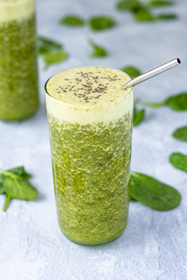 A large glass with a metal straw filled to the top with an energizing green smoothie, topped with chia seeds.