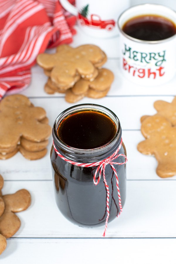 A glass jar of gingerbread simple syrup with a red and white bow on a table next to gingerbread cookies and mugs of coffee.