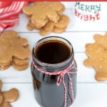 Pinterest Pin with text overlay 'Gingerbread Simple Syrup'. Image of a glass jar of dark colored syrup tied up with a red and white bow.