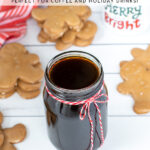 Pinterest Pin with text overlay 'Gingerbread Simple Syrup Perfect for Coffee and Holiday Drinks'. Image of a glass jar of dark colored syrup tied up with a red and white bow.