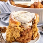 Pinterest Pin with text overlay 'Overnight Gingerbread Cinnamon Rolls'. Image of a gingerbread cinnamon roll on a small white plate.