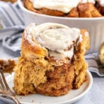 Pinterest Pin with text overlay 'Gingerbread Cinnamon Rolls'. Image of cinnamon roll on a plate with the outside ripped open revealing the inside.