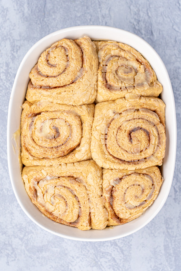 Risen cinnamon rolls in a white baking dish ready to be baked in the oven.