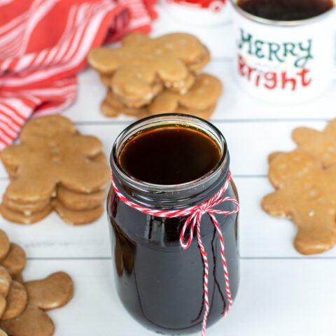 A glass jar of dark colored simple syrup sit-in non a table next to mugs of coffee and stacks of gingerbread cookies.