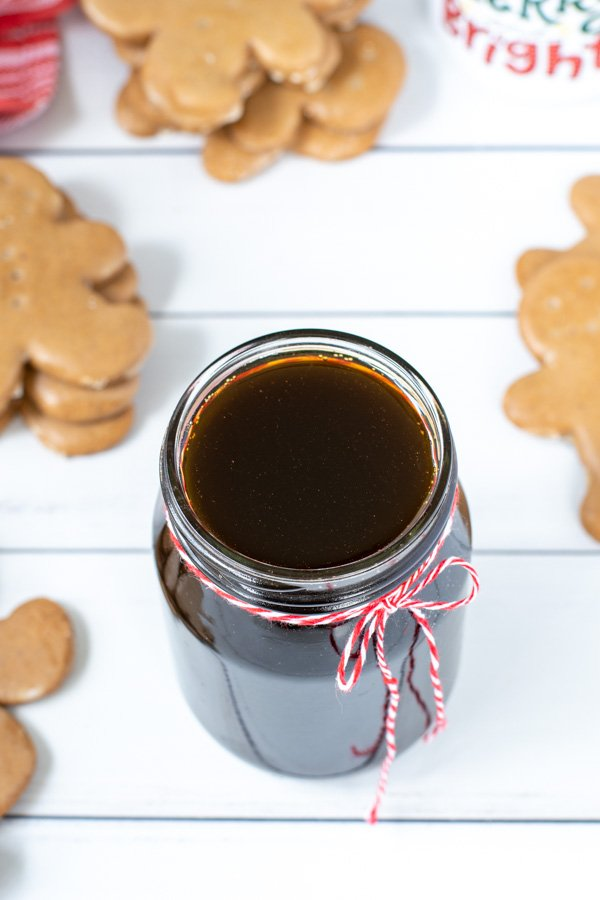 Close up of Gingerbread Syrup in a glass jar with a red and white string tied in a bow.