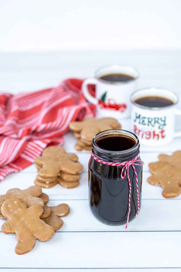 A glass jar of gingerbread simple syrup tied with a red and white string on a tale next to stacks of gingerbread cookies and mugs of coffee.