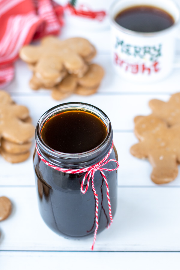 A styled shot of gingerbread syrup in a glass jar tied with a red and white string sitting next to stacks of gingerbread cookies and a mug of coffee.
