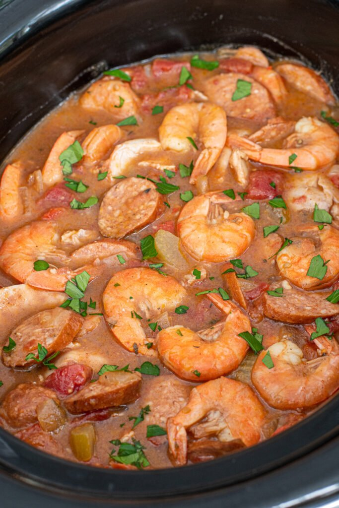 Close look inside a crockpot filled with cooked gumbo with shrimp and andouille sausages on the top.