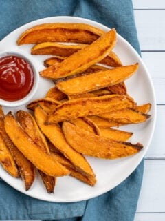 Close up of a white plate sitting on blue towel the plate in piled high with crispy sweet potato wedges and a little cup of ketchup.