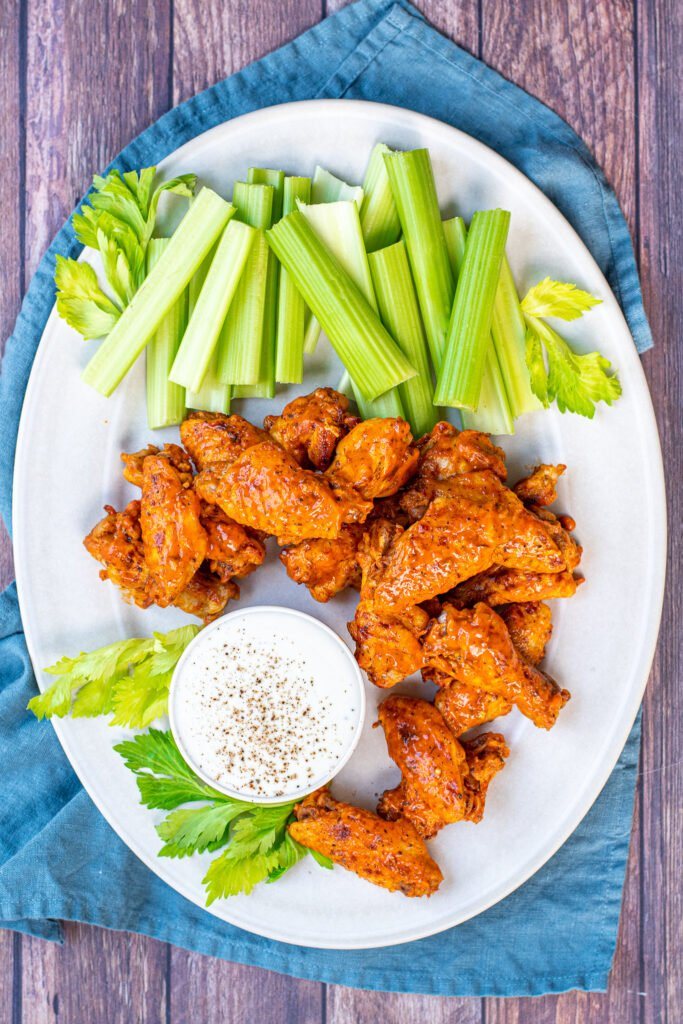 A large white platter holding pressure cooker hot wings, celery and a cup of ranch dressing.