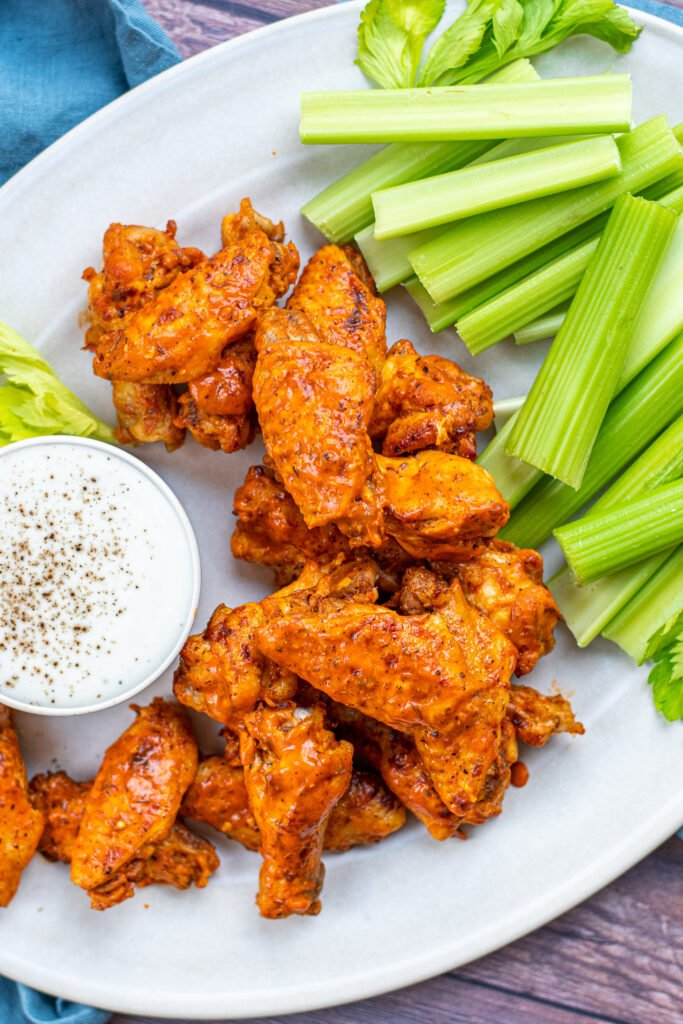 A large pile of chicken wings on a platter showing off sauces exteriors.