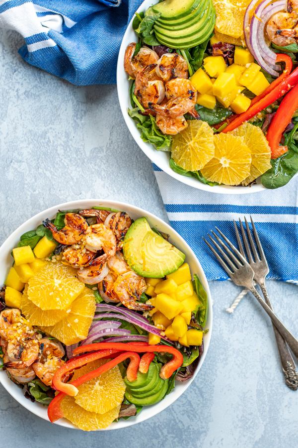 Overhead view of two large white bowls next to a bright blue towel, the bowls are filled with mixed greens, grilled shrimp, avocado, oranges, mango, and red bell pepper.
