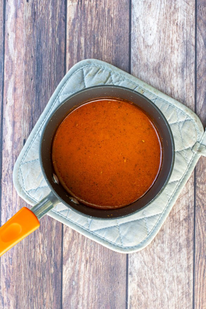 A small sauce pan holding the homemade hot wing sauce.