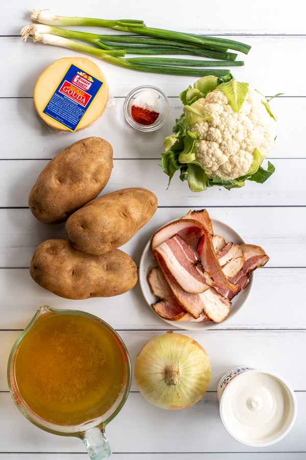 Ingredients needed to make loaded baked potato soup sitting on a white background.