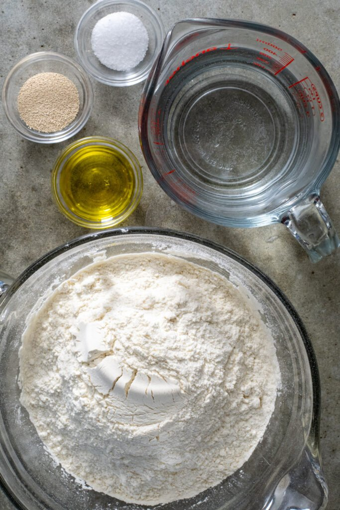 Ingredients including flour, water, olive oil, yeast, and salt laid out ready to be used to make pizza dough.