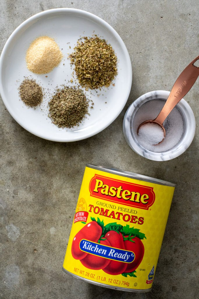 Ingredients needed to make pizza sauce including kitchen ready tomatoes, spices, and salt.